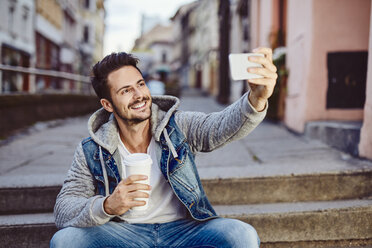 Man taking selfie holding coffee and sitting on stairs - BSZF00092