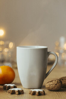 Cup of hot tea, tangerine, walnuts, and cinnamon stars - JHAF00004