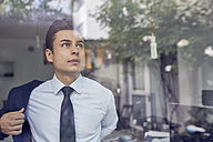 Portrait of young businessman behind glass pane in office putting on his jacket - PNEF00179