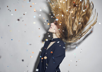 Young woman tossing hair under  shower of confetti - PNEF00185