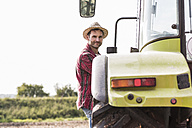 Portrait of confident farmer with tractor - UUF11922