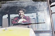 Portrait of confident farmer on tractor - UUF11925