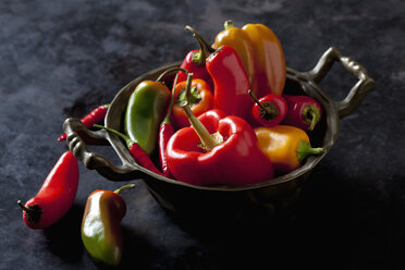 Bowl of various organic bell peppers and chili peppers on dark ground - CSF28357