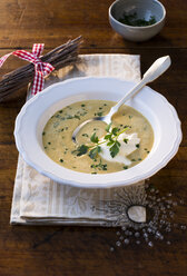 Dish of chestnut soup with cream and parsley on festively laid table - PPXF00109