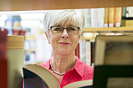 Portrait of smiling senior woman with  book in a city library - FRF00573