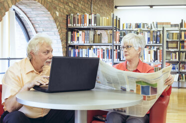Senior couple with laptop and newspaper in a city library - FRF00576