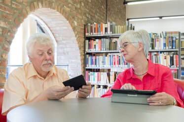 Senior couple with tablet and e-book in a city library - FRF00579