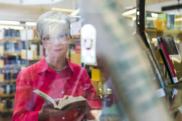 Portrait of senior woman behind glass pane in a city library - FRF00582