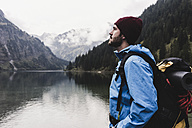 Austria, Tyrol, Alps, hiker standing at mountain lake - UUF11945