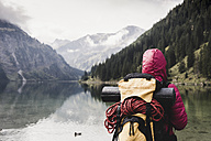 Austria, Tyrol, Alps, hiker standing at mountain lake - UUF11948