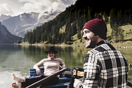 Austria, Tyrol, Alps, happy couple in rowing boat on mountain lake - UUF11957