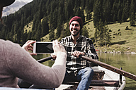 Austria, Tyrol, Alps, woman taking cell phone picture of smiling man in rowing boat on mountain lake - UUF11960