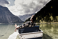 Austria, Tyrol, Alps, relaxed man in boat on mountain lake - UUF11963