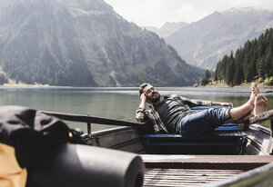 Austria, Tyrol, Alps, relaxed man in boat on mountain lake - UUF11966