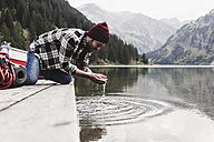 Austria, Tyrol, Alps, man kneeling on jetty scooping water from mountain lake - UUF11972