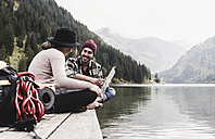 Austria, Tyrol, Alps, couple with map sitting on jetty at mountain lake - UUF11975