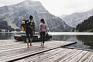 Austria, Tyrol, Alps, couple walking on jetty at mountain lake - UUF11978