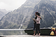 Austria, Tyrol, Alps, couple with map standing on jetty at mountain lake - UUF11981