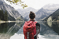Austria, Tyrol, Alps, hiker standing at mountain lake - UUF11987