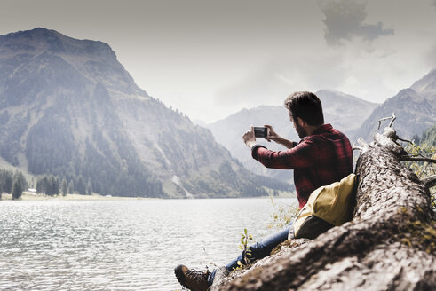 Austria, Tyrol, Alps, hiker sitting on tree trunk at mountain lake taking cell phone picture - UUF11993
