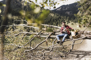Austria, Tyrol, Alps, hiker relaxing on tree trunk at mountain lake checking cell phone - UUF11996