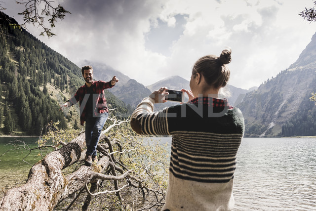Austria, Tyrol, Alps, woman taking cell phone picture of man balancing on tree trunk at mountain lake - UUF11999 - Uwe Umstätter/Westend61
