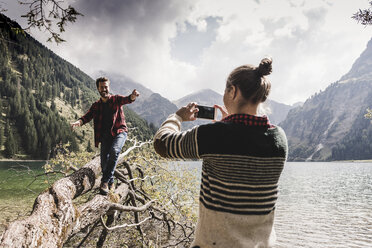 Austria, Tyrol, Alps, woman taking cell phone picture of man balancing on tree trunk at mountain lake - UUF11999