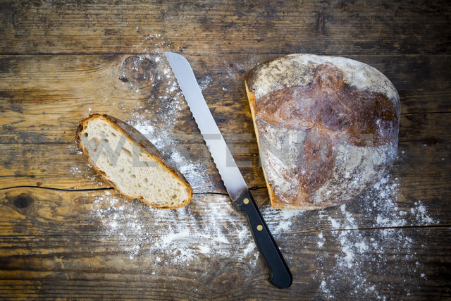Cut wheat bread powdered with flour and bread knife on dark wood - LVF06353