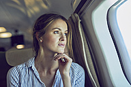 Serious woman looking out of airplane window - PNEF00213