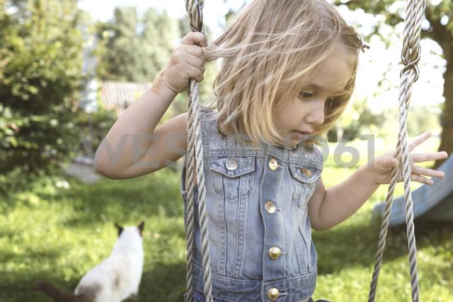Little girl sitting on swing in the garden - KMKF00021