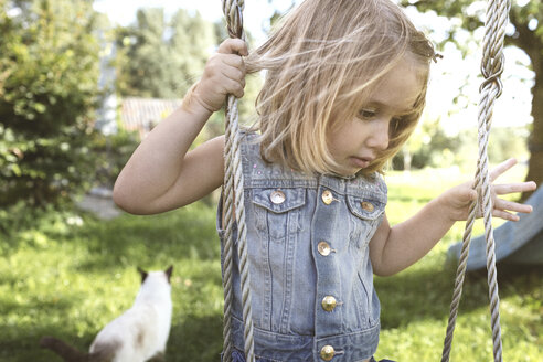 Little girl sitting on swing in the garden - KMKF00021