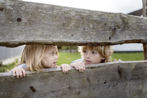 Brother and his little sister behind wooden fence - KMKF00024