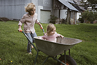 Boy pushing wheelbarrow with his little sister through the garden - KMKF00027