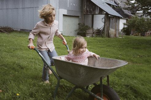 Boy pushing wheelbarrow with his little sister through the garden - KMKF00027