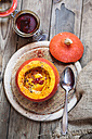 Creamed vegan pumpkin soup with chili in hollowed Hokkaido pumpkin on wooden board - SBDF03333