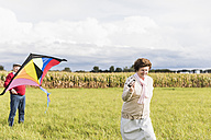 Senior couple flying kite in rural landscape - UUF12003