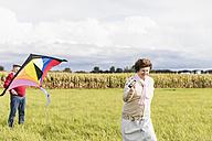 Senior couple flying kite in rural landscape - UUF12003