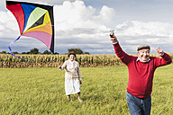 Happy senior couple flying kite in rural landscape - UUF12006