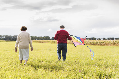 Senior couple walking with kite in rural landscape - UUF12009
