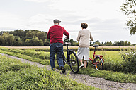 Senior couple pushing bicycles in rural landscape - UUF12012
