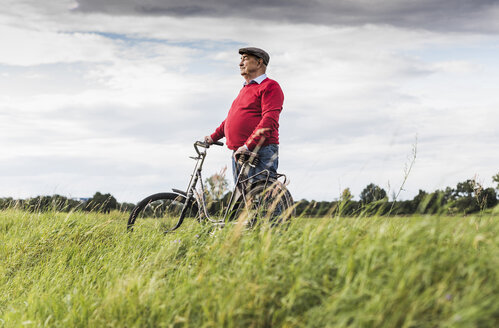 Senior man with bicycle in rural landscape - UUF12015