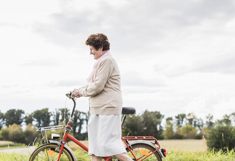 Senior woman pushing bicycle in rural landscape - UUF12021