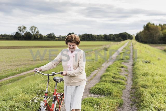 Senior woman pushing bicycle in rural landscape - UUF12024