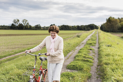 Senior woman pushing bicycle in rural landscape - UUF12024