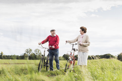 Senior couple pushing bicycles in rural landscape - UUF12027