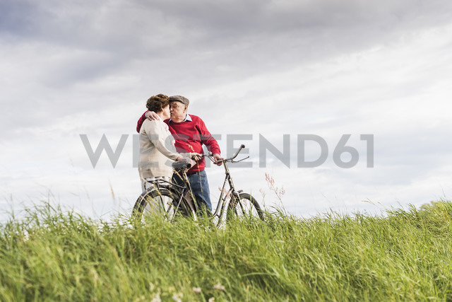 Senior couple with bicycles kissing in rural landscape - UUF12030