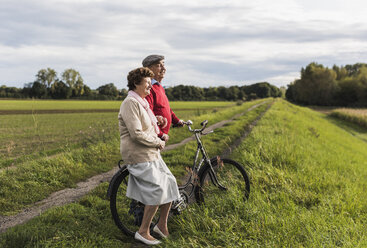 Senior couple with bicycles in rural landscape - UUF12033