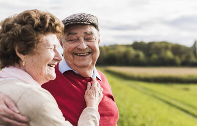 Happy senior couple embracing in rural landscape - UUF12036