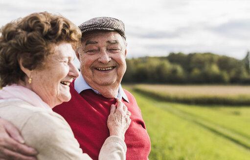 Happy senior couple embracing in rural landscape - UUF12036