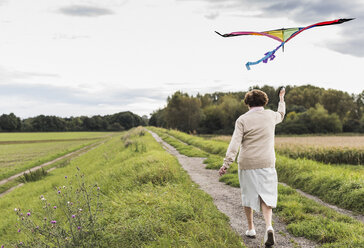 Senior woman walking with kite in rural landscape - UUF12042